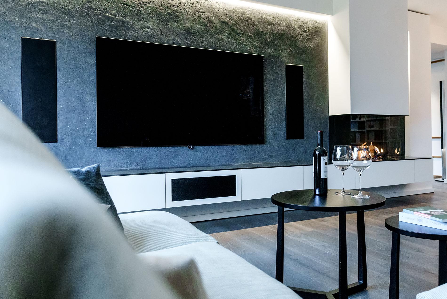 Wohnzimmer mit Gaskamin und Naturstein-Wand - Tischlerei Schöpker